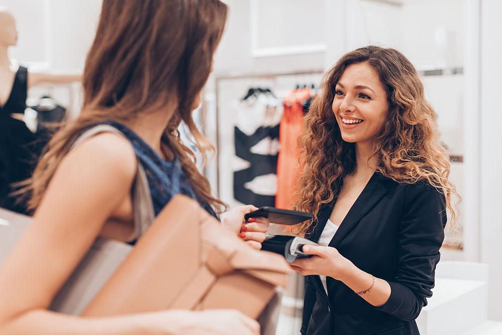 kunder betjenes av ansatt i klesbutikk