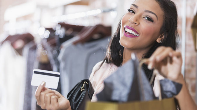 Close up of a young woman shopping in a clothing store. She is smiling at the camera, standing at the checkout counter holding a credit card and a handbag. She is lifting a shopping bag.