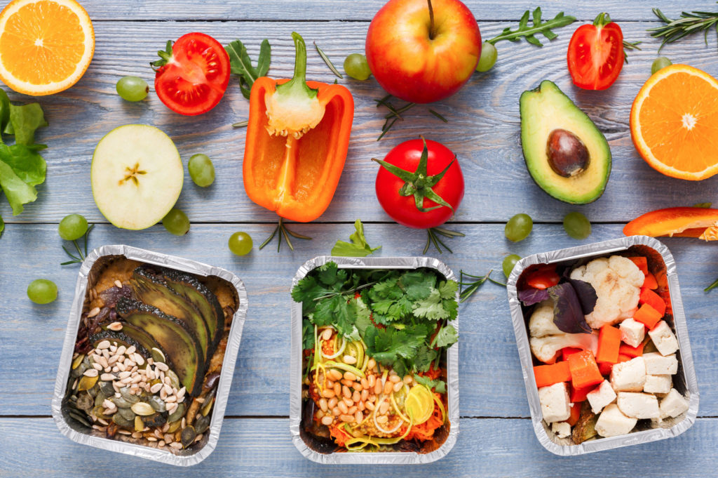 Fresh vegetables and fruits, foil lunch containers on blue wood background.