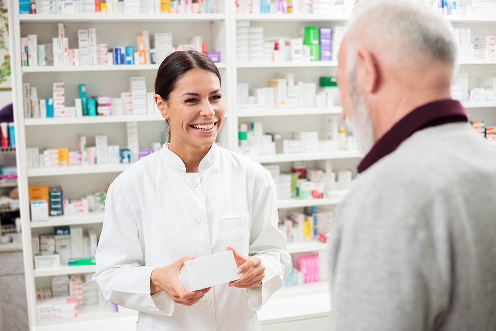 Female employee in pharmacy talking with old man.