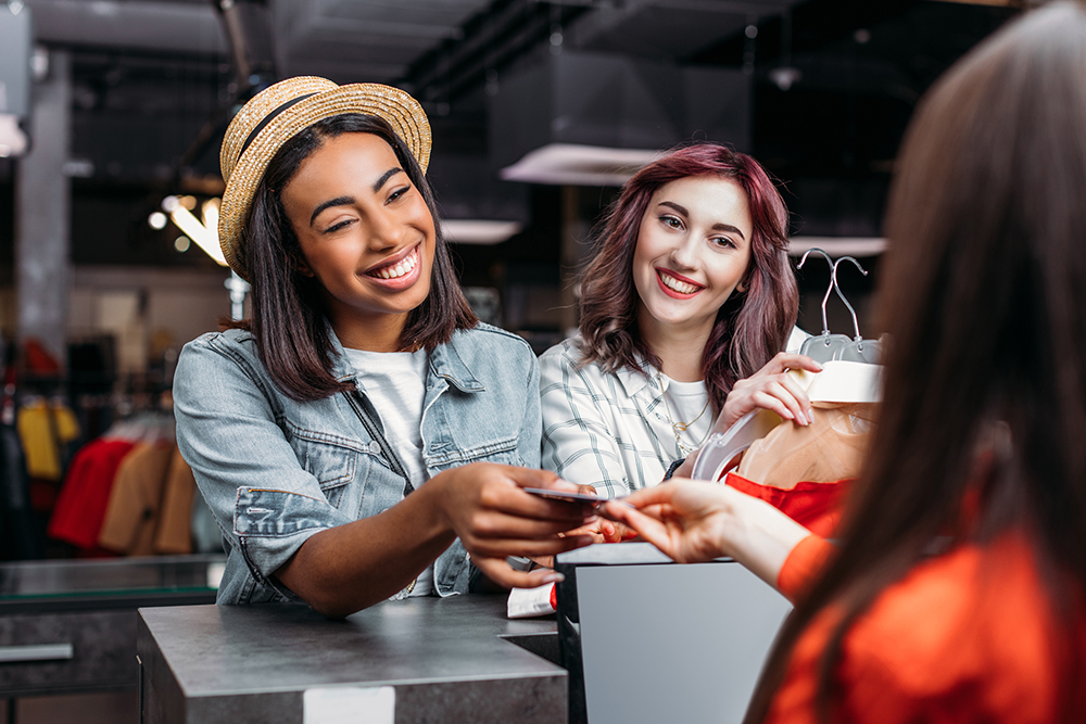 multicultural young girls shopping and paying with credit card in boutique.