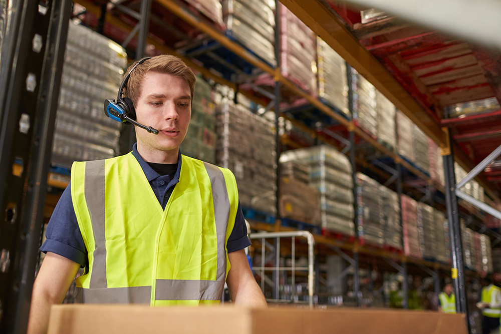 Man using pick by voice working in a  warehouse