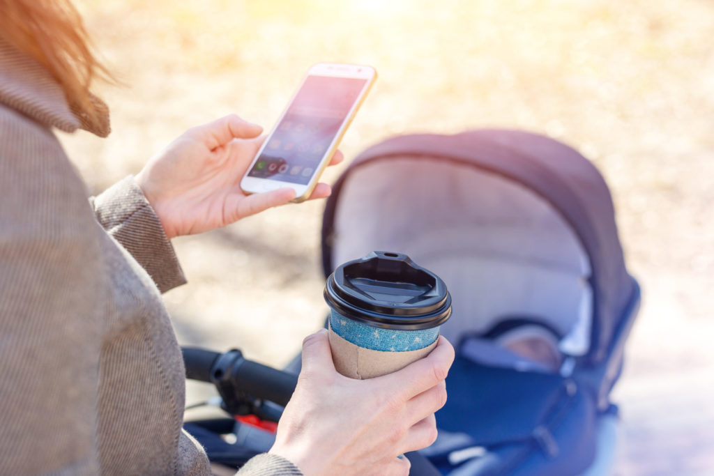 Woman using shopping list software on phone during walk with baby carriage